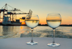 Dos vidrios del vino blanco fresco en el mantel blanco con las estructuras del puerto y del buque de carga en fondo borroso Fotos de archivo