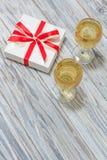 Dos vidrios del vino blanco y de un regalo Imagenes de archivo