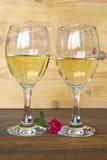 Dos vidrios del vino blanco y de una rosa Fotos de archivo