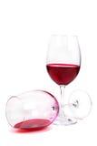 Dos vidrios del vino rojo uno de ellos mentiras Imagenes de archivo