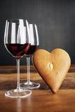 Dos vidrios del vino rojo y del pan de jengibre en forma de corazón Foto de archivo