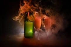 dos vidrios del vino y de la botella sobre fondo de niebla entonado Imagen de dos copas de vino con champán los esquemas y las si Foto de archivo