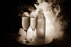 dos vidrios del vino y de la botella sobre fondo de niebla entonado Imagen de dos copas de vino con champán los esquemas y las si Imágenes de archivo libres de regalías