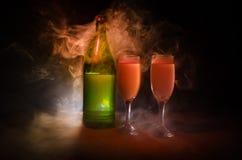 dos vidrios del vino y de la botella sobre fondo de niebla entonado Imagen de dos copas de vino con champán los esquemas y las si Fotos de archivo libres de regalías