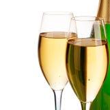 Dos vidrios elegantes del champán en el fondo del verde embotellan el primer aislado en un blanco Aún vida festiva Imagen de archivo