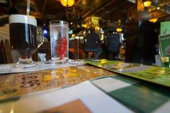 Dos vidrios en la tabla que contiene el agua con las bayas rojas y Guinn Fotos de archivo