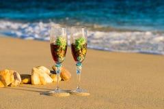 Dos vidrios en una ola del mar en la playa Fotos de archivo