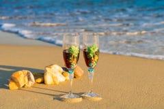Dos vidrios en una ola del mar en la playa Imagen de archivo