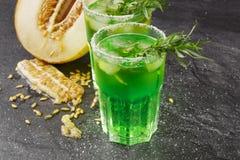 Dos vidrios enormes de bebidas sin alcohol con las hojas del hielo y del estragón y el melón delicioso del corte en un fondo negr Foto de archivo libre de regalías
