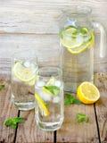 Dos vidrios grandes de limonada fría con el hielo, limón, hojas de menta Imagenes de archivo