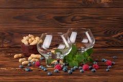 Dos vidrios grandes vacíos Arándanos frescos jugosos, frambuesas, cacahuetes en un cuenco y menta en un fondo de madera del marró Fotos de archivo libres de regalías