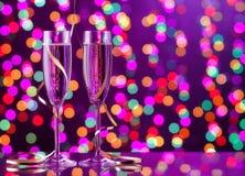 Dos vidrios llenos del champán con el bokeh se encienden en el fondo Fotografía de archivo