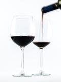 Dos vidrios transparentes exquisitos con el vino rojo y un vino de colada de la botella en un fondo blanco Imagen de archivo