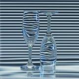 Dos vidrios vacíos con las bandas de las persianas de la refracción Foto de archivo libre de regalías