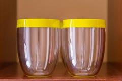 Dos vidrios vacíos con los casquillos amarillos Imagenes de archivo