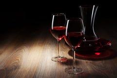 Dos vidrios y jarras de vino en un vector de madera Imagenes de archivo