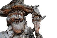 Dos viejos gnomos, guardas del bosque, esculpieron en un tronco Fotos de archivo libres de regalías