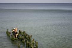 Dos viejos hombres están pescando en un embarcadero roto viejo Fotografía de archivo