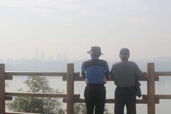 Dos viejos hombres que miran el cielo contaminado de la ciudad Foto de archivo