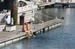 Dos viejos hombres que se sientan en tomar el sol portuario, con sus pies en el mar fotografía de archivo libre de regalías