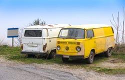 Dos viejos y los coches de la furgoneta del vintage de Volkswagen Beetle del grunge parquearon el si Imagen de archivo libre de regalías