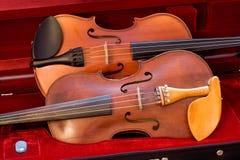 Dos violines de lado a lado en un caso Foto de archivo libre de regalías