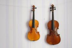 Dos violines rotos lamentables viejos de un diverso tamaño para la ejecución de la restauración en la pared con el espacio de la  Imagen de archivo libre de regalías