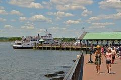 Dos visitantes están disfrutando del día mientras que otros visitantes están haciendo cola en Liberty Island para las travesías d Fotos de archivo