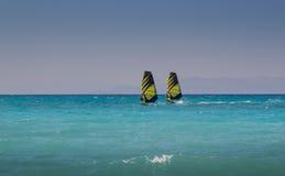 Dos windsurfers montan paralelo en el mar Foto de archivo