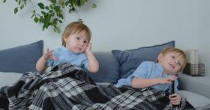 Dos 4 y 2 años de los muchachos, están viendo la TV el sentarse en el sofá Un programa de televisión emocionante Historietas de l almacen de video