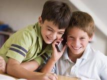 Dos Young Boys que llaman alguien en un teléfono celular Imagen de archivo