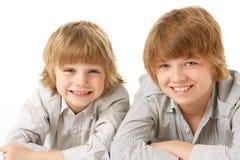 Dos Young Boys que mienten en el estómago en estudio Fotografía de archivo libre de regalías