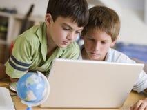 Dos Young Boys usando una computadora portátil en el país Imagenes de archivo