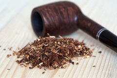 Dose of dry Tobacco and Pipe on wooden Background Stock Photos
