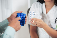 Daily dose pills. Doctor shows the patient how to use daily dose pills Royalty Free Stock Photography