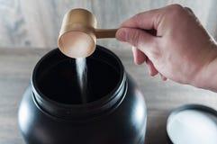 Doser εκμετάλλευσης χεριών και χύνοντας συμπλήρωμα τροφίμων Στοκ φωτογραφία με δικαίωμα ελεύθερης χρήσης