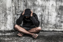 dosieren Sie asiatischen männlichen Drogenabhängigen mit Problemen, Mann in der Haube mit über stockbilder