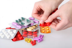 Dosing medicaments. Hand dosing a medicaments from colorful blisters Royalty Free Stock Images