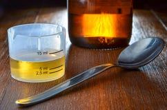 Dosis del jarabe de la tos con la taza de medida, la cuchara y la botella del medicin Fotos de archivo