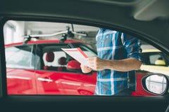 Doskonalić linie Młody ciemnowłosy brodaty mężczyzna egzamininuje samochód przy przedstawicielstwem handlowym i robi jego wyborow Fotografia Stock