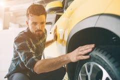Doskonalić linie Młody ciemnowłosy brodaty mężczyzna egzamininuje samochód przy przedstawicielstwem handlowym i robi jego wyborow Zdjęcie Stock