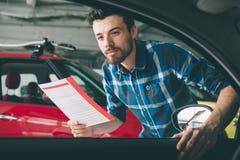 Doskonalić linie Młody ciemnowłosy brodaty mężczyzna egzamininuje samochód przy przedstawicielstwem handlowym i robi jego wyborow Fotografia Royalty Free