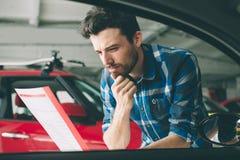 Doskonalić linie Młody ciemnowłosy brodaty mężczyzna egzamininuje samochód przy przedstawicielstwem handlowym i robi jego wyborow Zdjęcia Royalty Free