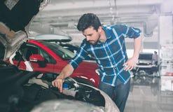 Doskonalić linie Młody ciemnowłosy brodaty mężczyzna egzamininuje samochód przy przedstawicielstwem handlowym i robi jego wyborow Zdjęcia Stock