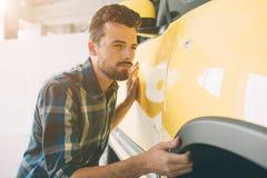 Doskonalić linie Młody ciemnowłosy brodaty mężczyzna egzamininuje samochód przy przedstawicielstwem handlowym i robi jego wyborow Obrazy Stock