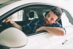 Doskonalić linie Młody ciemnowłosy brodaty mężczyzna egzamininuje samochód przy przedstawicielstwem handlowym i robi jego wyborow Obraz Royalty Free