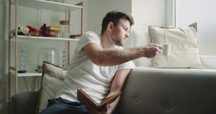 Doskonalić ranek dla młodego faceta czyta książkę i pije kawę, na kanapa nieociosanym projekcie zbiory wideo