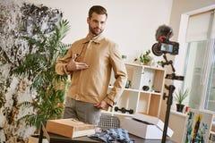 Doskonalić spojrzenie! Młody męski mody blogger jest ubranym elegancką kurtkę podczas gdy magnetofonowy nowy wideo przegląd dla Y zdjęcie stock