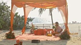 Dossel do casamento decorado com o pano vermelho na praia do oceano filme