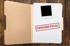 Dossier avec les papiers confidentiels sur la table en bois Images stock